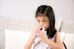 Gulligt liten flickadricksvatten på soffan hemma bakgrund suddighetdde den skyddande pillen för maskeringen för hälsa för omsorgs royaltyfria bilder