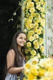 Gulligt liten flickaleende med mycket gul ros royaltyfria foton