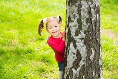 Gulligt liten flickanederlag bak enormt träd Arkivbild