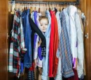 Gulligt liten flickanederlag inom garderob från henne föräldrar Arkivbild