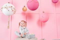 Gulligt liten flickasammanträde i en stol och öppnar en ask med en gåva för bakgrundsjulgran med prydnader _ Royaltyfri Bild