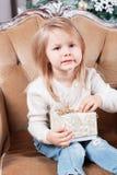Gulligt liten flickasammanträde i en stol och öppnar en ask med en gåva för bakgrundsjulgran med prydnader Royaltyfri Bild