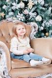 Gulligt liten flickasammanträde i en stol och öppnar en ask med en gåva för bakgrundsjulgran med prydnader Fotografering för Bildbyråer