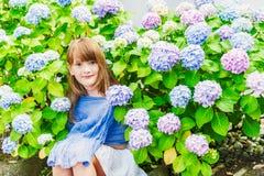 Gulligt liten flickasammanträde mellan blommor Fotografering för Bildbyråer