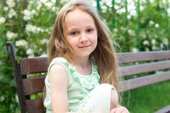 Gulligt liten flickasammanträde på bänk i trädgård Royaltyfria Bilder
