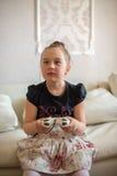 Gulligt liten flickasammanträde på soffan och spelavideospelen Royaltyfria Foton