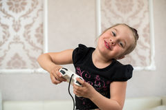 Gulligt liten flickasammanträde på soffan och spelavideospelen Arkivfoto