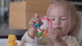 Gulligt liten flickasammanträde på tabellen som spelar med leksaken och ler på kameran lager videofilmer