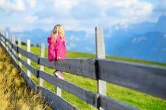 Gulligt liten flickasammanträde på trästaketet som beundrar härligt landskap i Dolomitesbergskedja royaltyfria bilder