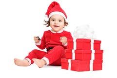 Gulligt liten flickasammanträde vid en hög av julgåvor Fotografering för Bildbyråer