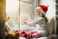 Gulligt liten flickasammanträde vid fönstret med en bokstav till Santa Claus Royaltyfri Fotografi