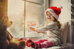 Gulligt liten flickasammanträde vid fönstret med en bokstav till Santa Claus Royaltyfri Bild