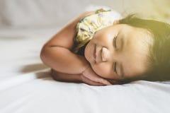 Gulligt litet asiatiskt litet barn som sover på hennes säng royaltyfri foto