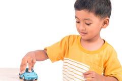 Gulligt litet asiatiskt förskolebarn för pojkebarnunge som spelar leksakbilen royaltyfri foto
