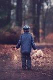 Gulligt litet barn, hållande lykta och nallebjörn i skog Arkivfoto