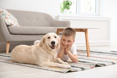 Gulligt litet barn med hans husdjur på golv fotografering för bildbyråer