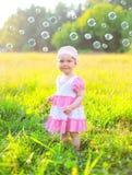 Gulligt litet barn på gräset med många såpbubblor Arkivfoton