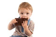 Gulligt litet barn som äter hans stora chokladstång Arkivbild