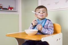 Gulligt litet barn som äter yoghurt Fotografering för Bildbyråer