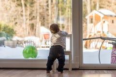 Gulligt litet litet barn som balanserar på en stol Arkivbild