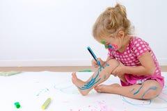 Gulligt litet barn som försiktigt målar henne ben Arkivfoton