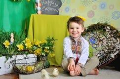 Gulligt litet barn som ler fira påsk målat gräs för 2 placerade allt för easter för hinkfågelungebegreppet blommor ägg barn royaltyfri foto