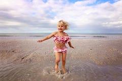 Gulligt litet barn som plaskar och spelar i vattnet p? stranden vid havet arkivbild