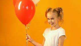 Gulligt litet barn som rymmer kulöra ballonger och ler på kameran, b-dag hälsning stock video