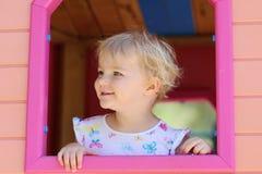 Gulligt litet barnflickanederlag i lekstuga på lekplatsen Royaltyfri Bild