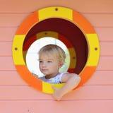 Gulligt litet barnflickanederlag i lekstuga på lekplatsen Arkivbilder