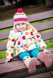 Gulligt litet barnflickasammanträde på bänken Arkivfoton