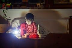 Gulligt litet caucasian barn, pojke, läsebok i säng royaltyfri fotografi