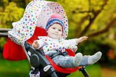 Gulligt litet härligt behandla som ett barn flickan av 6 månader som sitter i den stilfulla pram- eller sittvagn- och vänta påmam Royaltyfri Foto