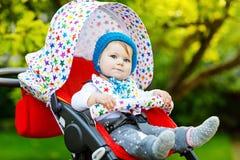 Gulligt litet härligt behandla som ett barn flickan av 6 månader som sitter i den stilfulla pram- eller sittvagn- och vänta påmam Fotografering för Bildbyråer