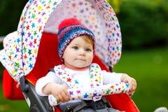 Gulligt litet härligt behandla som ett barn flickan av 6 månader som sitter i den stilfulla pram- eller sittvagn- och vänta påmam Arkivbild