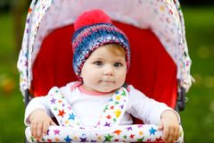 Gulligt litet härligt behandla som ett barn flickan av 6 månader som sitter i den stilfulla pram- eller sittvagn- och vänta påmam Arkivbilder
