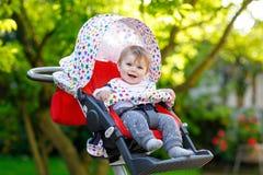 Gulligt litet härligt behandla som ett barn flickan av 6 månader som sitter i pram- eller sittvagn- och vänta påmamman Royaltyfri Fotografi