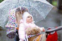 Gulligt litet härligt behandla som ett barn flickasammanträde i pramen, eller sittvagnen på kall dag med regnar snöslask, regnar  Arkivfoton