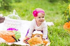Gulligt litet lyckligt behandla som ett barn flickan med den stora bruna nallebjörnen på äng för grönt gräs, våren eller sommarsä Arkivfoto
