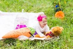 Gulligt litet lyckligt behandla som ett barn flickan med den stora bruna nallebjörnen på äng för grönt gräs, våren eller sommarsä Royaltyfria Foton