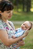 Gulligt litet nyfött behandla som ett barn barnet på att gå för moderhänder som är utomhus- Royaltyfria Foton