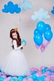 Gulligt litet prinsessaflickaanseende bland ballonger i rum över vit bakgrund se kameran Barndom Arkivfoto