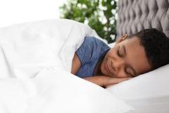 Gulligt litet sova för afrikansk amerikanpojke arkivfoton