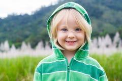 Gulligt lyckligt barn i hoodie framme av ett fält arkivbild