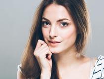 Gulligt mjukt rent le för härlig stående för ung kvinna trycka på hennes haka vid attraktiv grå bakgrund för fingrar Royaltyfri Foto