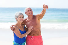Gulligt mogna par som omfamnar på stranden Royaltyfri Foto