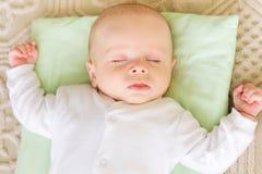 Gulligt nyfött behandla som ett barn att sova i säng Arkivbilder