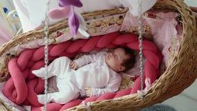 Gulligt nyfött behandla som ett barn att sova i vagga arkivfilmer