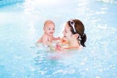 Gulligt nyfött behandla som ett barn ha gyckel i simbassäng Arkivfoto