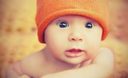 Gulligt nyfött behandla som ett barn i stuckit orange hattlock royaltyfri bild